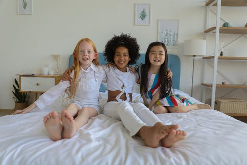 Happy cute little diverse girls with bare feet resting on cozy soft bed in modern comfortable room