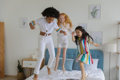 Happy diverse girls in casual outfit jumping on bed
