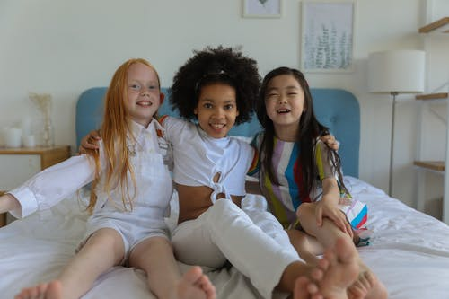 Adorable multiracial little girls embracing and having fun on ved together in modern comfortable room