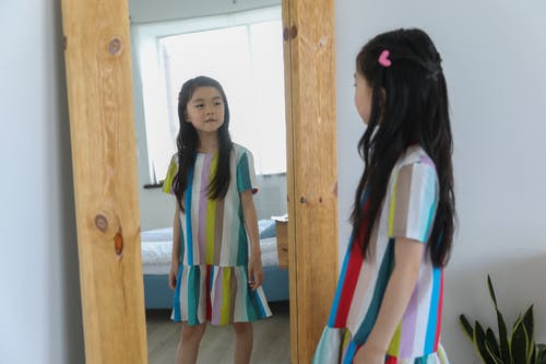 Adorable Asian girl looking at mirror with timber frame