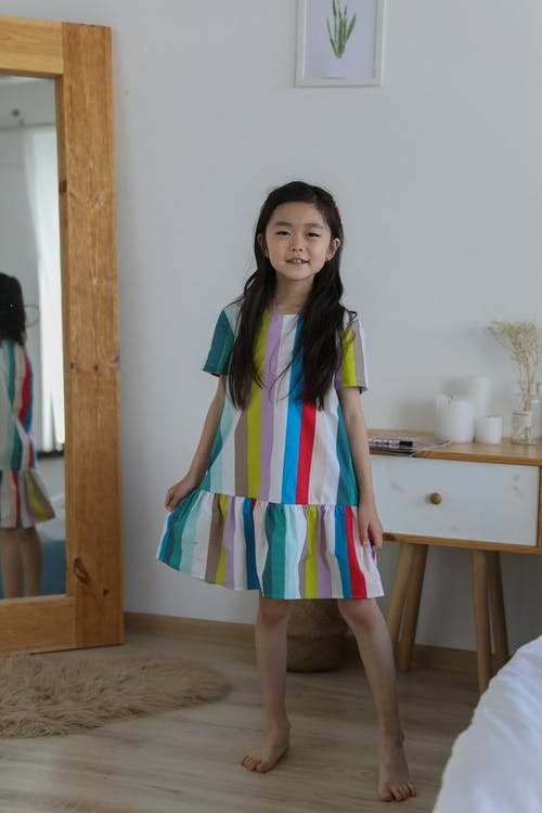 Happy Asian girl in colorful dress dancing in room