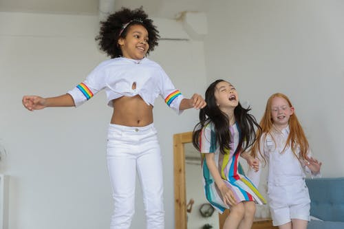 Cheerful positive multiracial girls in casual outfit laughing and jumping in modern room
