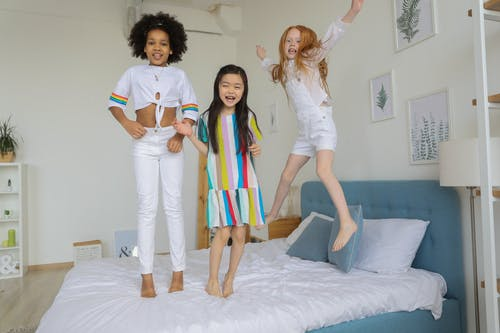 Multiracial smiling girls jumping on soft cozy bed