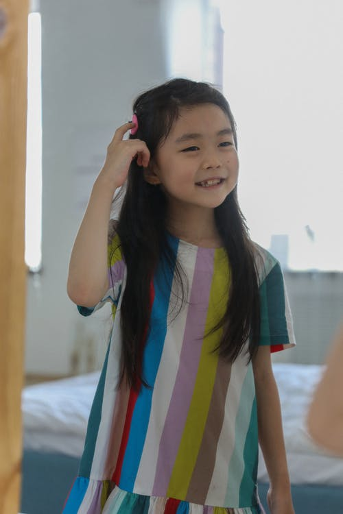 Adorable cheerful Asian girl in bright home dress looking at mirror and enjoying hairdo