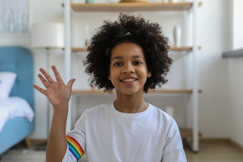Happy black girl waving hand at camera