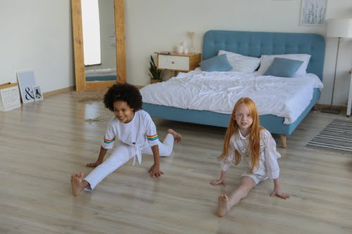 High angle of multiracial girls spending time at home and showing splits together on floor