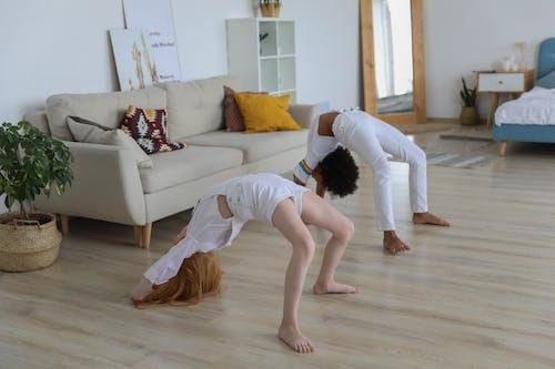 Girls doing backbend in light apartment