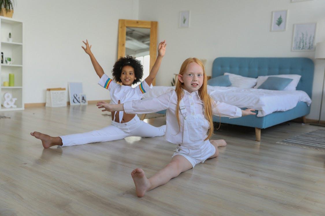 Full body multiracial girls performing splits happily sitting on floor in light bedroom