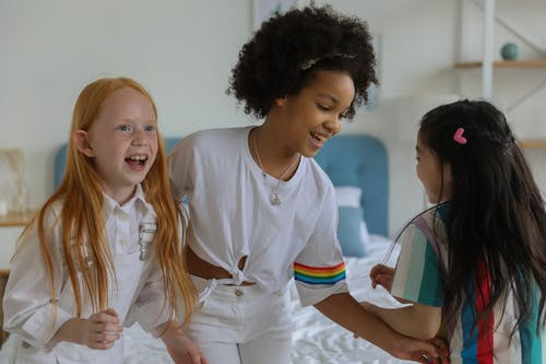 Group of multiracial girls spending time at home and laughing happily on bed