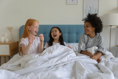 Laughing girls under blanket in bed
