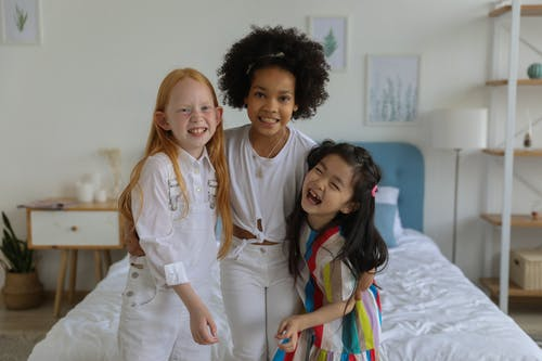 Group of multiethnic charming girls having fun and hugging while standing at bed in apartment