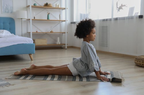 Focused black girl stretching on rug
