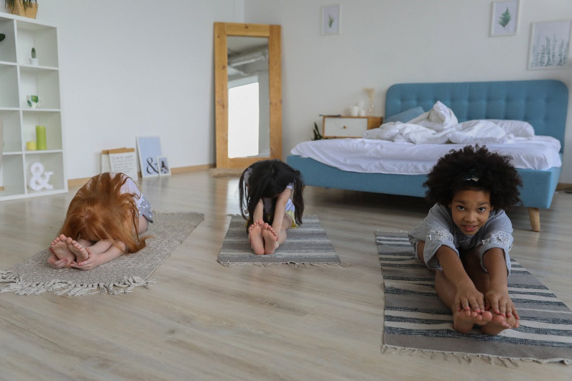 Little diverse girlfriends sitting on rugs and practicing Seated Forward Bend in light bedroom