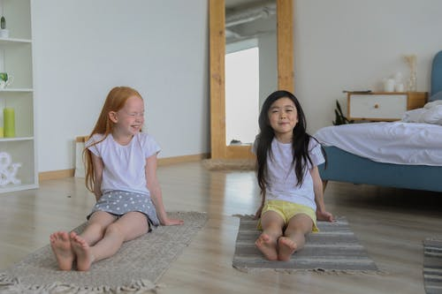 Charming diverse girls on rugs during yoga