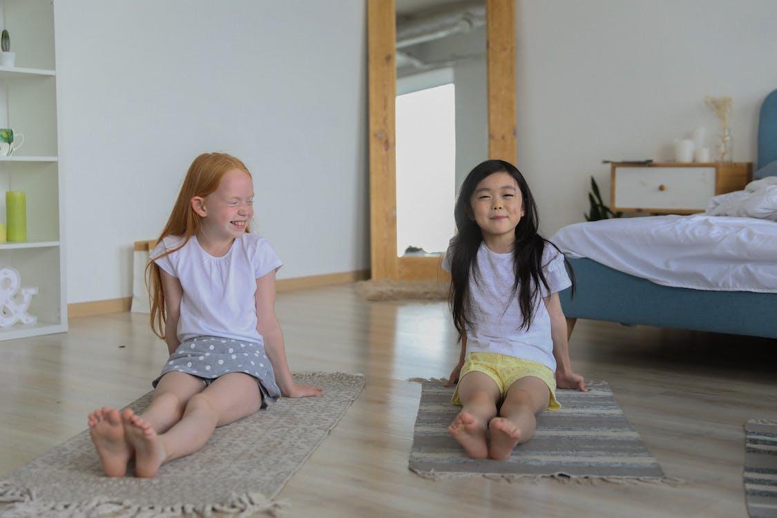 Charmante Verschiedene Mädchen Auf Teppichen Während Des Yoga