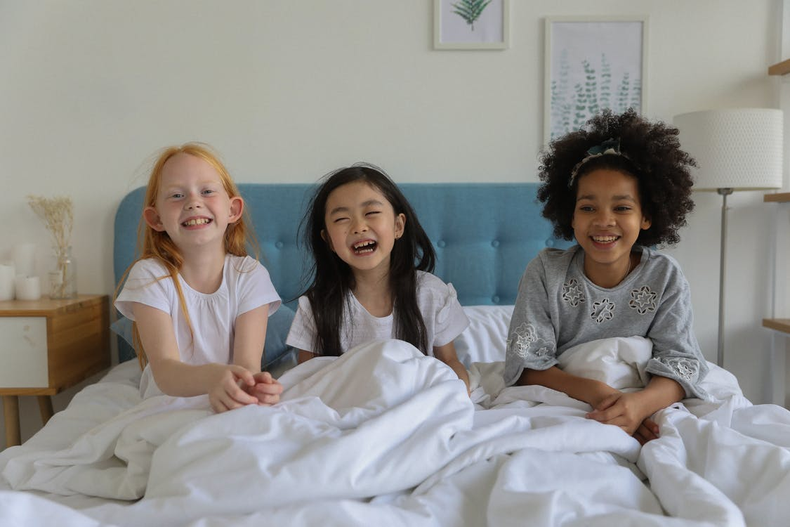 Laughing multiethnic best friends enjoying time during sleepover lounging under blanket in bed