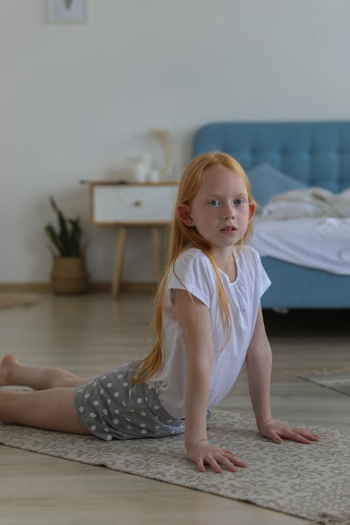Cute girl on rug practicing pose