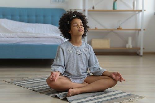 Black child meditating on carpet in room