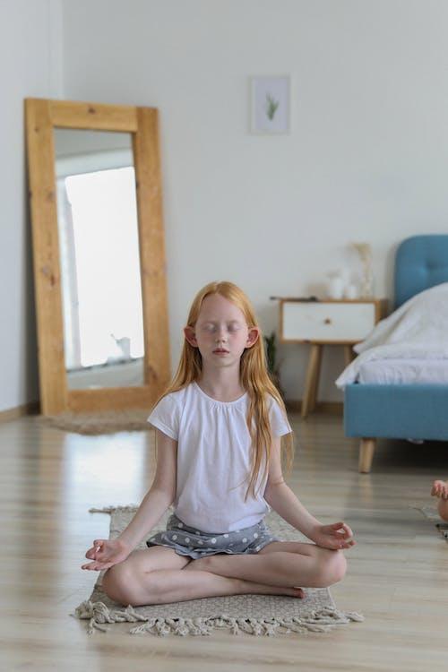 Focused girl meditating on carpet in bedroom