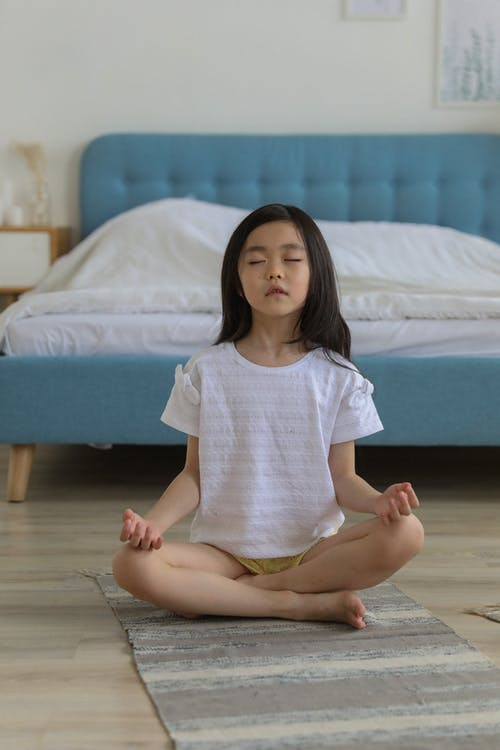 Asian girl meditating in room in daytime