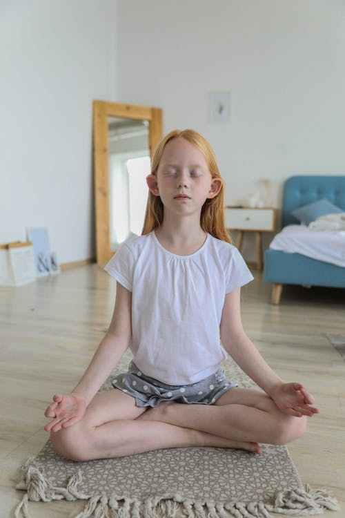 Focused girl meditating while practicing yoga Lotus pose