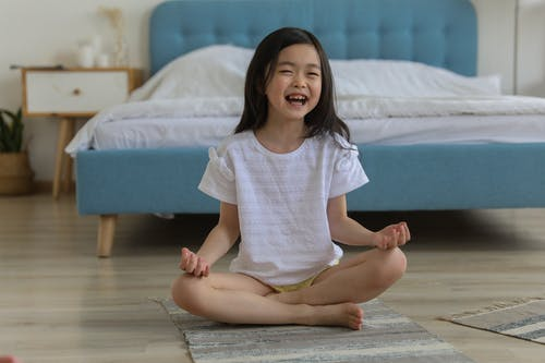 Happy Asian girl laughing while resting in room with legs crossed