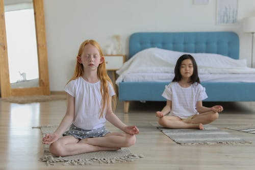 Girls with reddish and black hair meditating in room