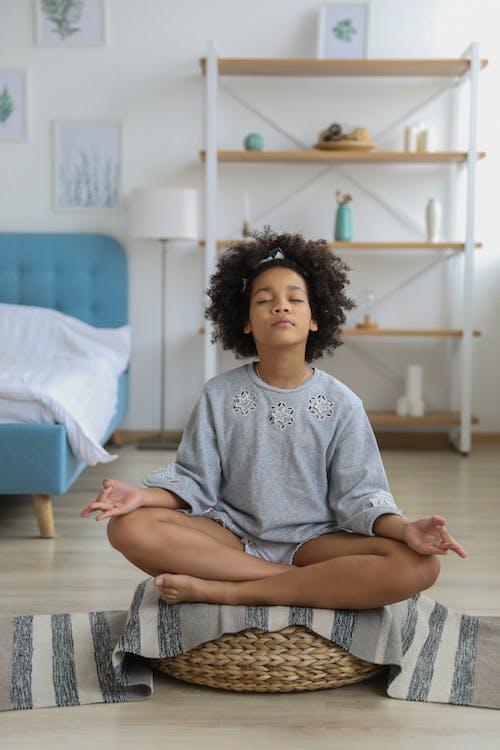 Black girl meditating with eyes closed