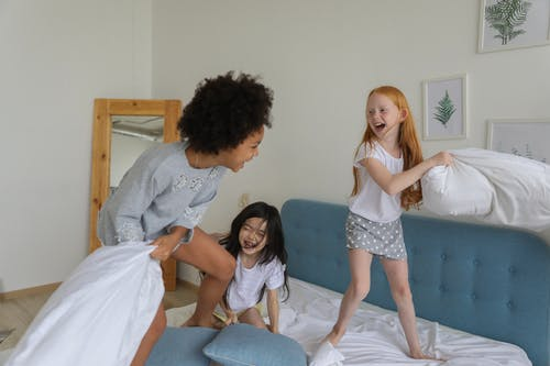 Cheerful girls fighting with pillows on bed