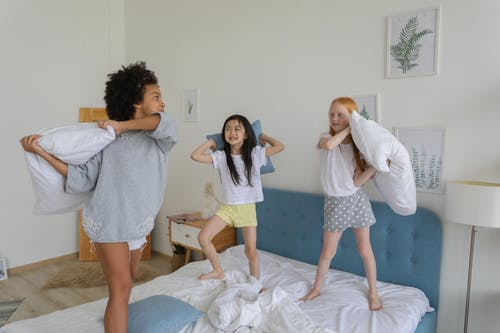 Full body of cheerful multiracial girls using pillows while playing in bright cozy room in daytime