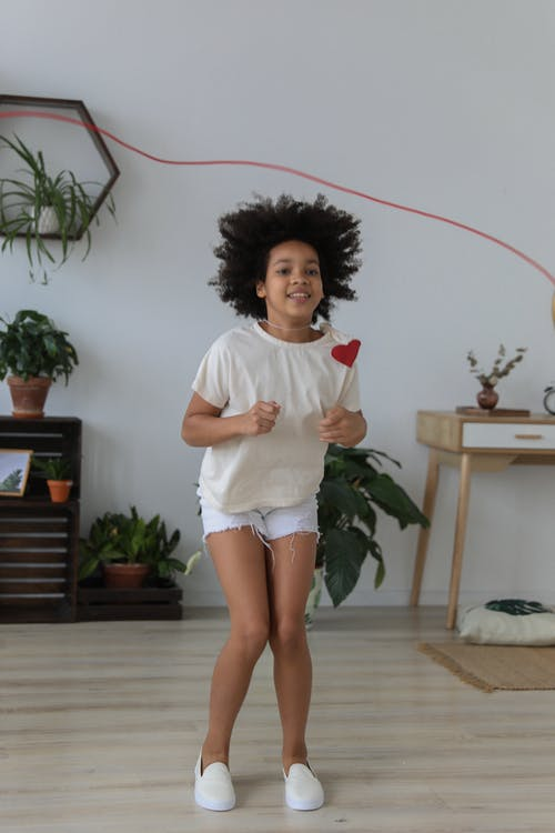 Happy black girl jumping over rope in bright room
