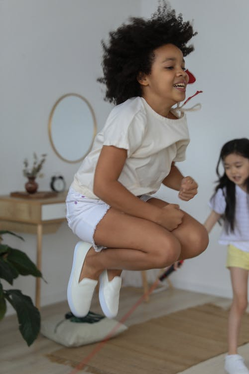 Cute black little girl jumping at home