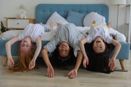 Cheerful multiracial children in casual clothes lying on comfortable bed while spending free time together