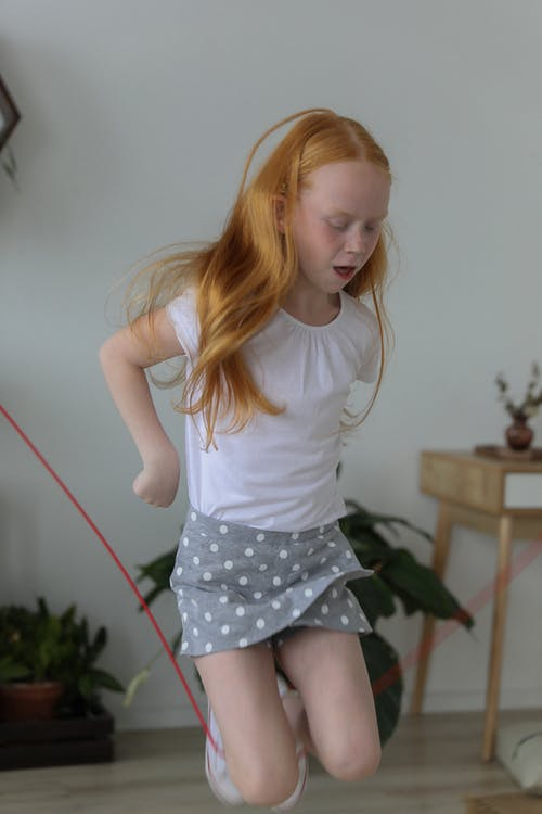 Cute little girl jumping rope at home