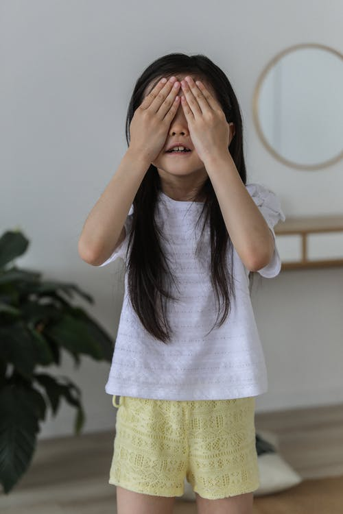 Cute little girl in casual clothes standing and hiding face behind hands while playing in cozy room