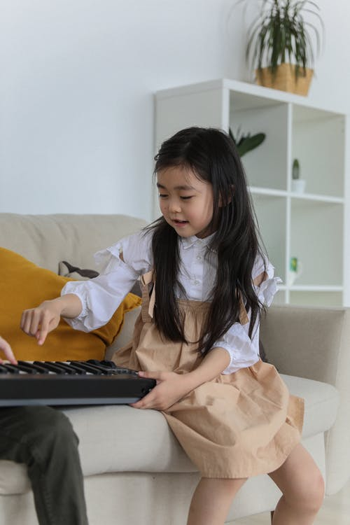 Cute Asian little girl playing synthesizer