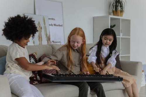 Happy multiracial little girls playing synthesizer