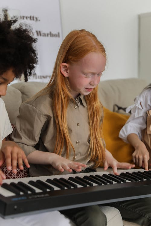 Happy child in casual clothes playing musical instrument with multiethnic friends at home