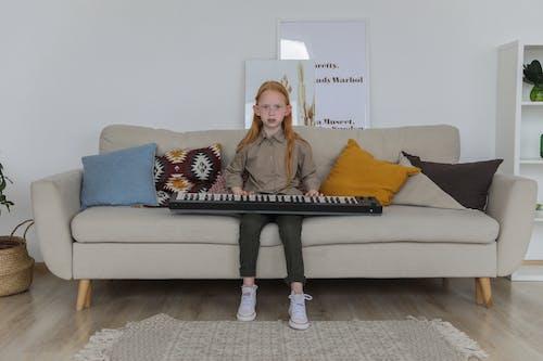 Stylish little girl with synthesizer on sofa