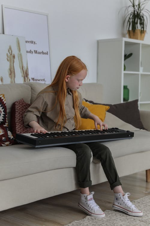 Little girl with synthesizer on sofa