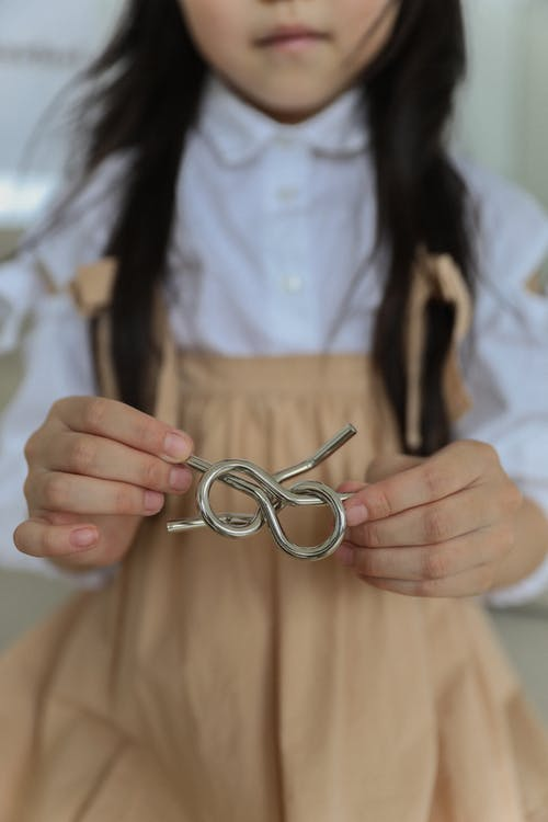 Crop faceless child in casual clothes holding metal wire brain teaser while playing at home