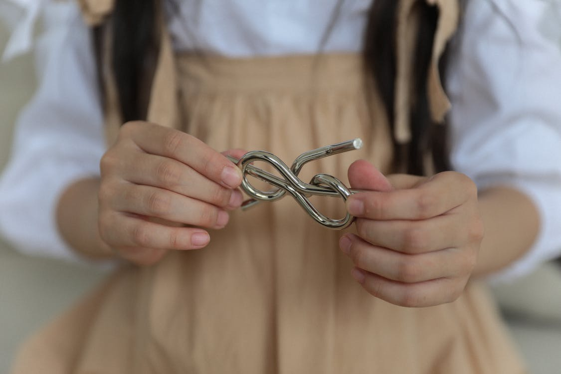 Crop anonymous child in casual wear holding metal wire brain teaser in shape of knot while playing at home