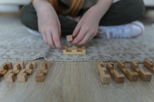 Crop girl playing blocks on carpet