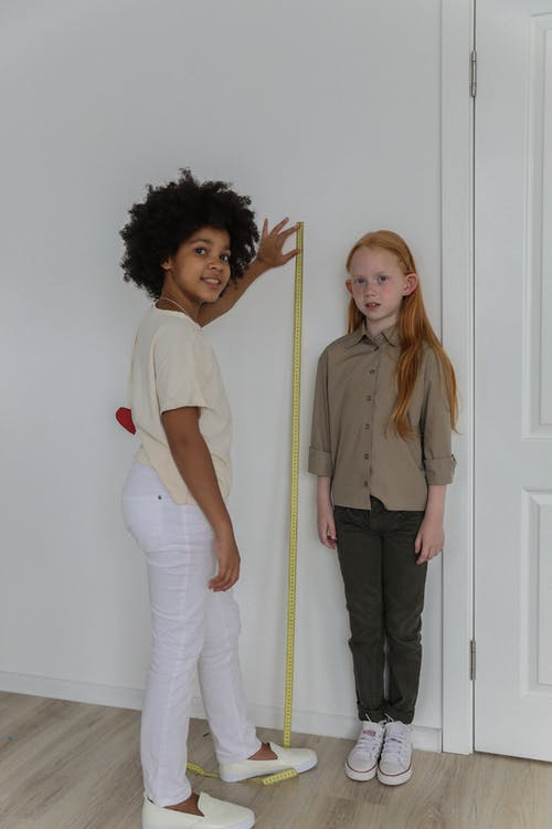 Cheerful multiracial girls measuring each other
