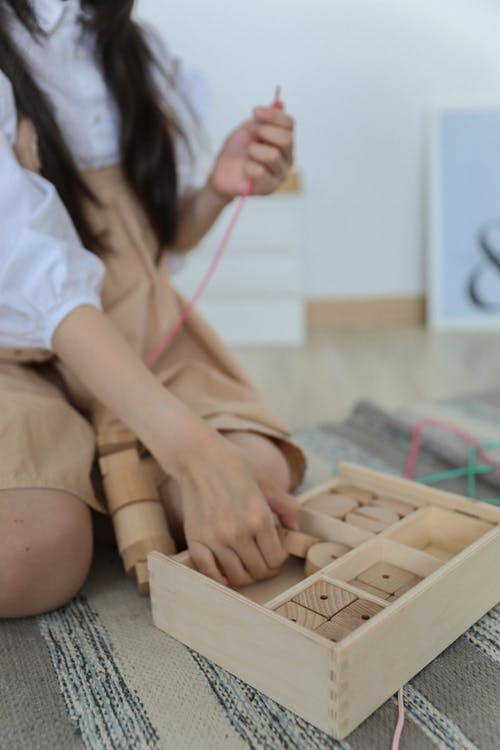 Crop child playing with blocks on floor