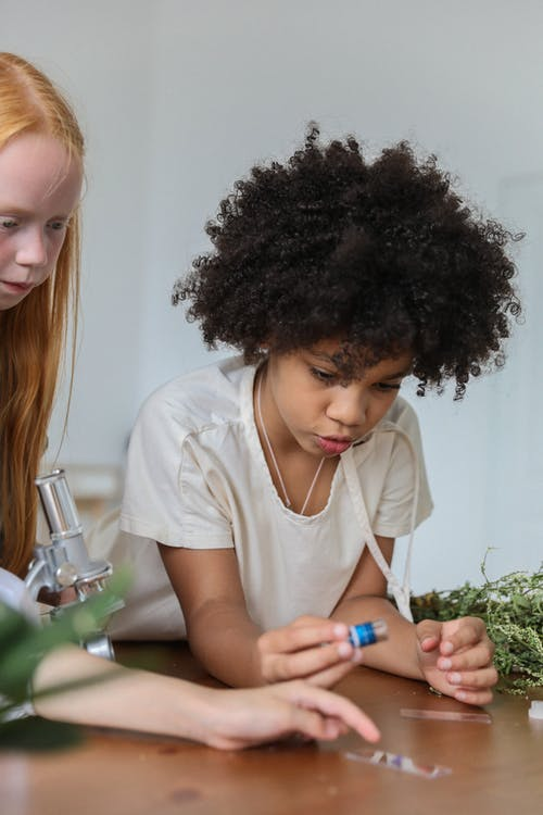 Multiracial little girls with microscope and vials