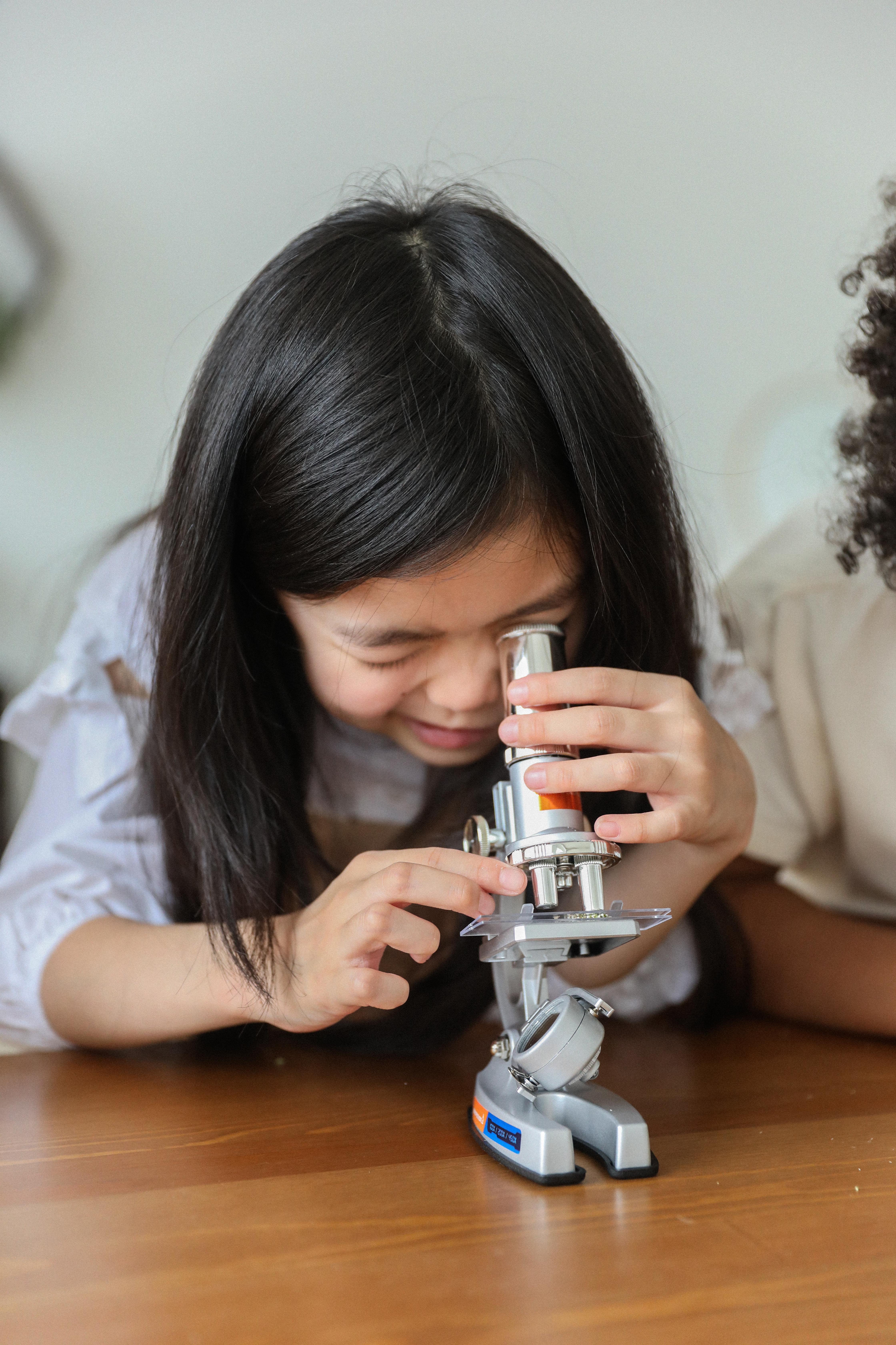 curious ethnic child examining chemical instruments in studio