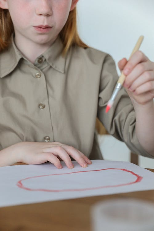 Serious kid painting oval on paper with watercolor