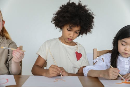 Focused diverse little girls painting with brushes in art studio