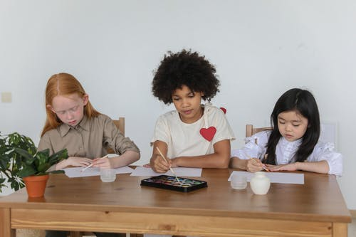 Group of adorable multiracial schoolgirls sitting at wooden table and drawing together with aquarelle during lesson